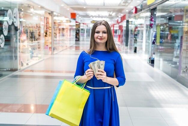 쇼핑백과 달러 지폐를 가진 여자