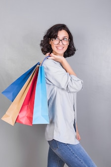Woman with shopping bags behind back