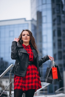 Woman with shopping bags by shopping center outside in winter