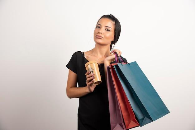 Donna con borse della spesa e tazza di caffè in posa sul muro bianco.