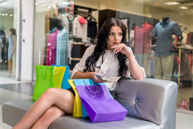 Woman with shopping bags and dollar fan in mall