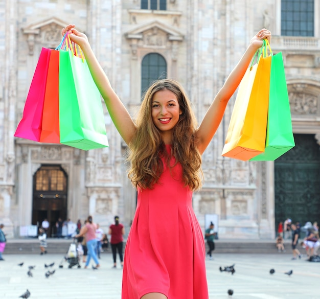 Женщина с хозяйственными сумками, наслаждаясь покупками в милане в италии