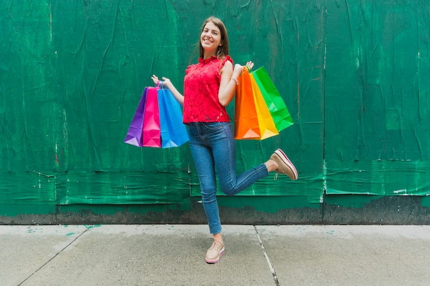 Woman with shopping bags on green wall background