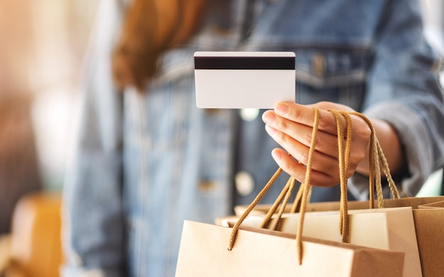 A woman with shopping bags holding and using a credit card for purchasing