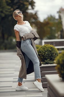 Женщина с хозяйственными сумками в летнем городе