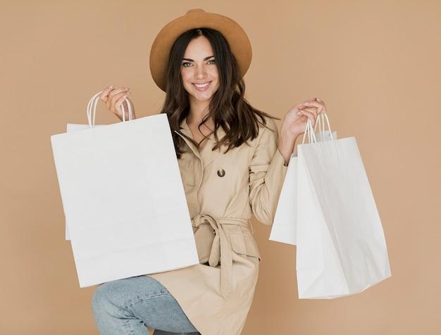 両方の手で買い物袋を持つ女性