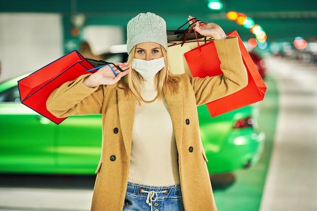 Женщина с сумками в маске на подземной автостоянке
