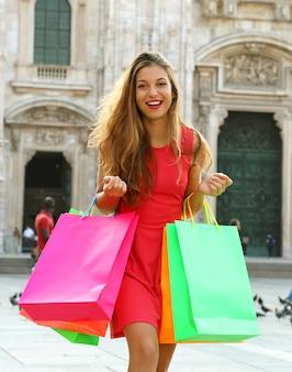 Женщина с хозяйственными сумками в милане в италии
