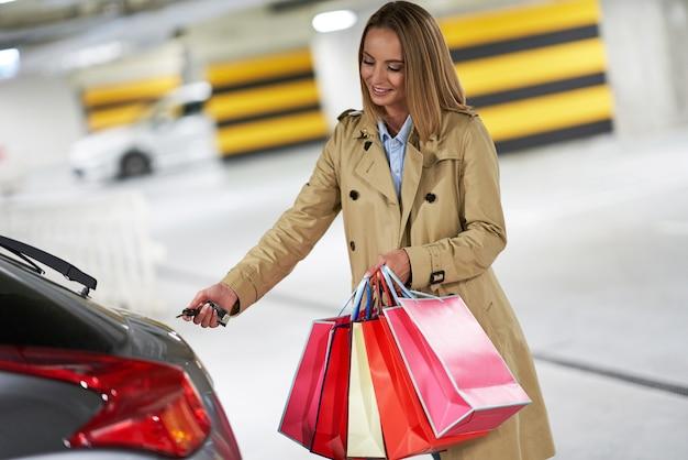 Женщина с хозяйственными сумками на подземной автостоянке
