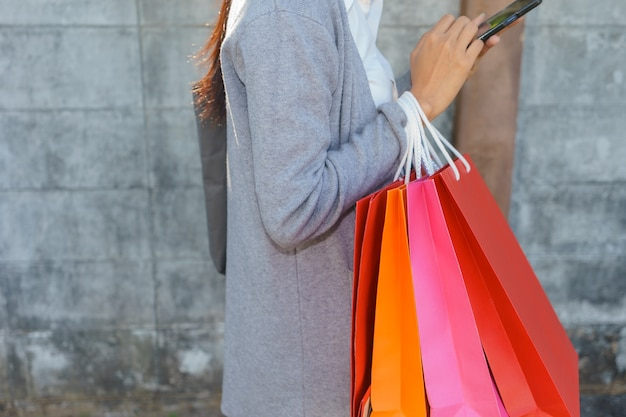 Woman with shopping bags is tapping on mobile phone for online shopping.