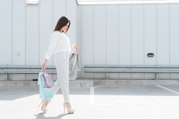 Woman with shopping bags is walking on road.