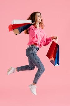 Женщина с хозяйственными сумками прыгает