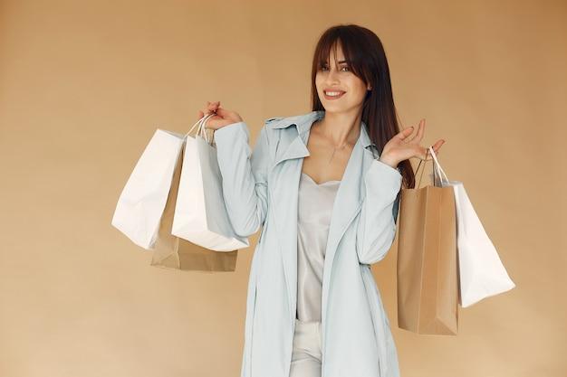 買い物袋を持つ女性。ベージュの壁の女性。青いジャケットの女性。