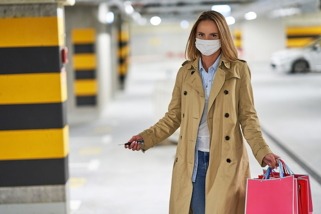 Woman with shopping bags in mask in underground parking lot
