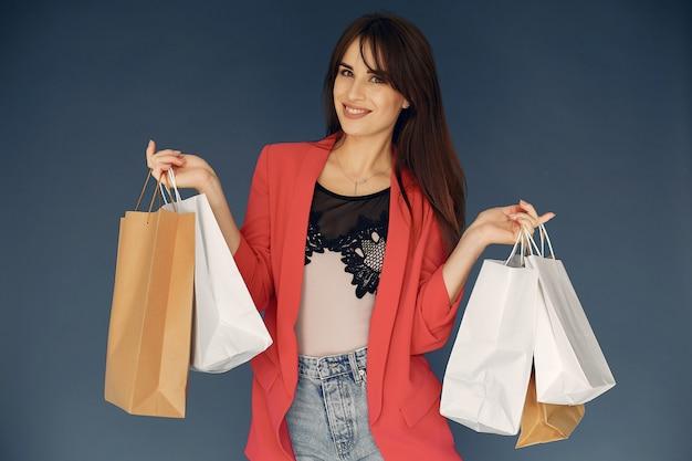 青色の背景に買い物袋を持つ女性