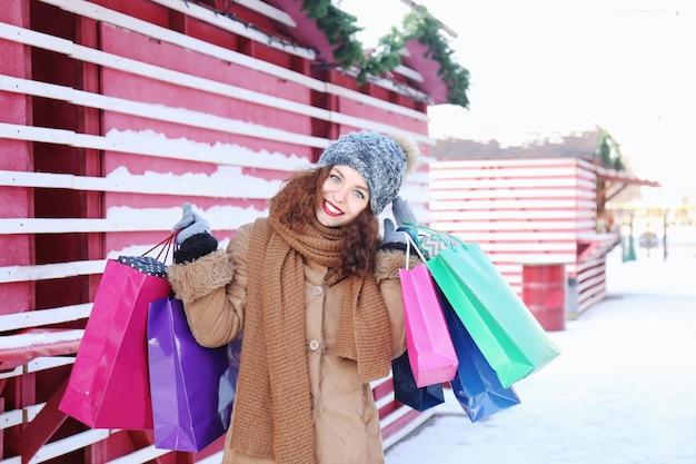 Женщина с хозяйственными сумками на рождественской ярмарке