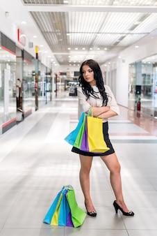Женщина с хозяйственными сумками позирует в проходе торгового центра