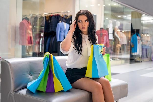 쇼핑몰에서 소파에 앉아 쇼핑 가방을 가진 여자