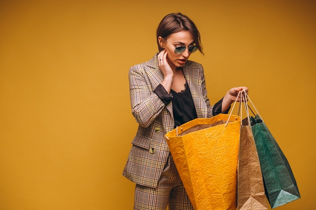 Woman with shopping bags in studio on yellow background isolated