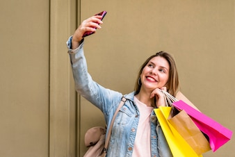 Woman with shopping bags taking selfie at wall
