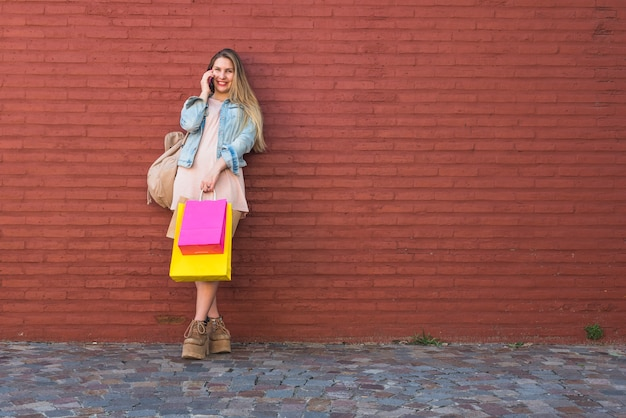 Woman with shopping bags talking by phone at wall