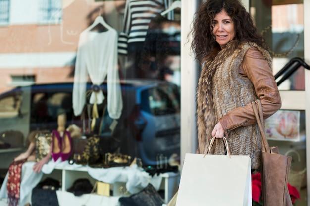 ブティックで歩くショッピングバッグを持つ女性