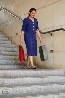 階段を歩いて買い物袋を持つ女性