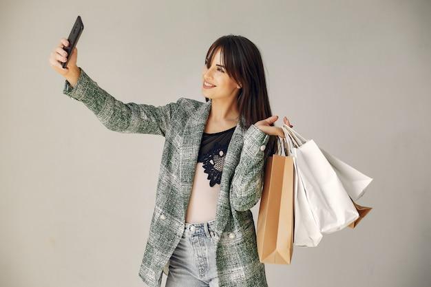 Donna con i sacchetti della spesa su un fondo bianco