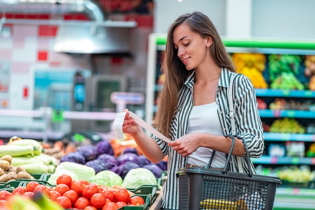 Woman with shopping basket checks and examines a sales receipt after purchasing food in a grocery store. customer buying products at supermarket