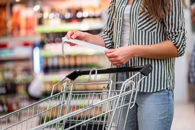 Woman with shopping cart in aisle checks and examines a sales receipt after purchasing food in a grocery store. customer purchase products at supermarket.