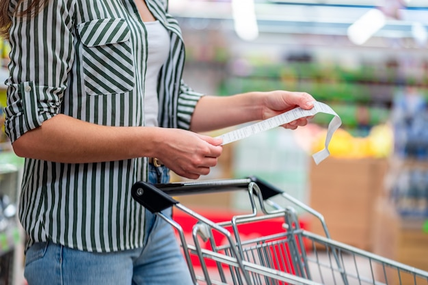 Woman with shopping cart in aisle checks and examines a sales receipt after purchasing food in a grocery store