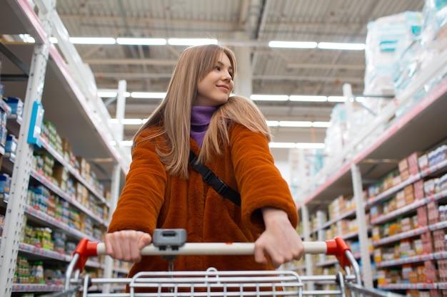 소매점 선반에서 쇼핑 카트를 가진 여자