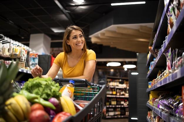 슈퍼마켓에서 음식을 구입하는 쇼핑 카트를 가진 여자