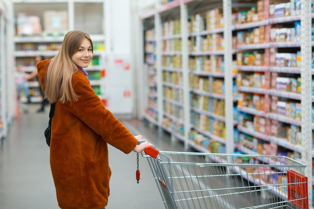 Woman with shopping cart at retail store shelves with food