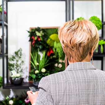 A woman with short blond hair chooses a bouquet in a flower shop