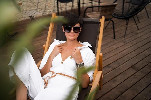 白い服とサングラスの短いブルネットの髪を持つ女性。ファッションストリート写真。ファッションモデルは座っているし、茶色の木製の背景にリラックスします。