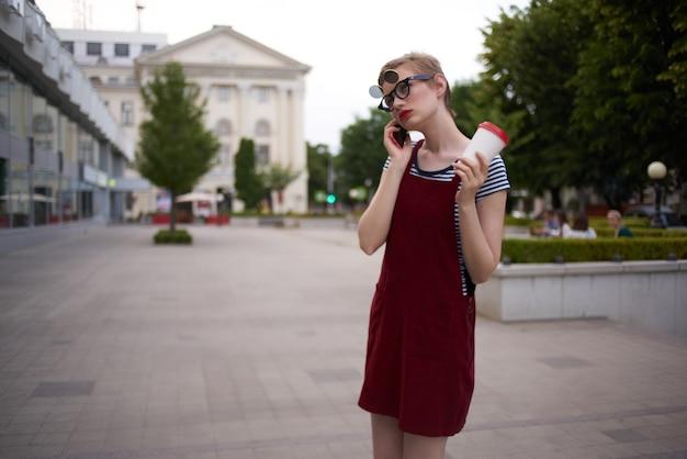 短い髪の女性と屋外で新鮮な空気を歩くコーヒーのグラス