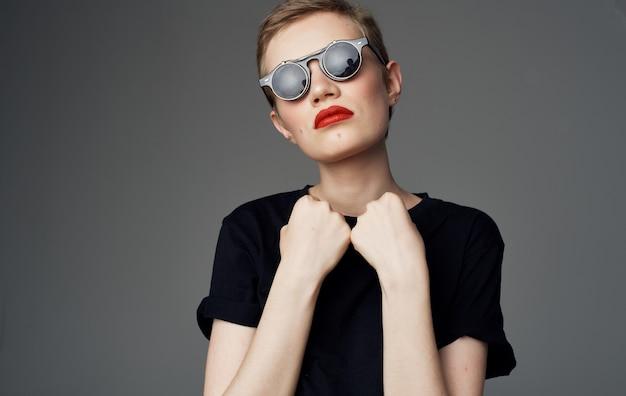 짧은 머리와 어두운 안경 메이크업 붉은 입술 매력적인 클로즈업을 가진 여자.
