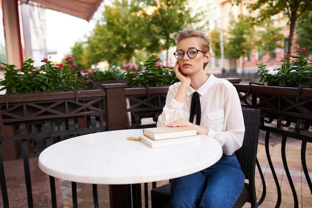 本のあるカフェのテーブルで短い髪の女性