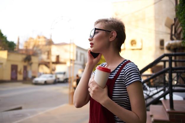 電話で話しているメガネとコーヒーの短い髪のカップを持つ女性