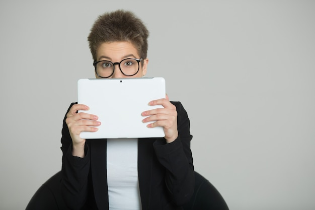 Woman with short hair on her head, in a suit and glasses with a tablet in her hands in a man's image