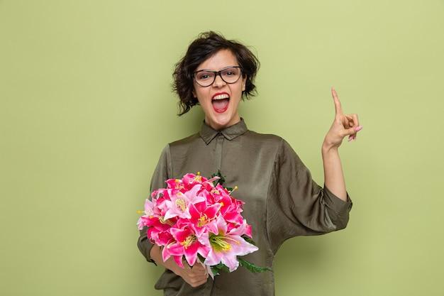 Женщина с короткими волосами держит букет цветов, глядя в камеру, счастливая и взволнованная, показывая указательный палец, празднуя международный женский день 8 марта, стоя на зеленом фоне