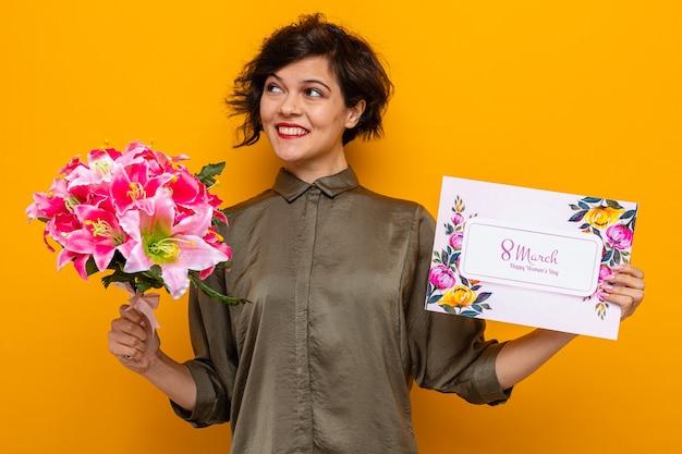 Женщина с короткими волосами, держащая поздравительную открытку и букет цветов, счастливая и веселая улыбающаяся, отмечает международный женский день 8 марта, стоя на оранжевом фоне