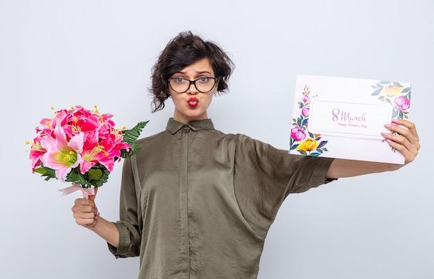 Женщина с короткими волосами, держащая поздравительную открытку и букет цветов, выглядит смущенной и недовольной, празднует международный женский день 8 марта