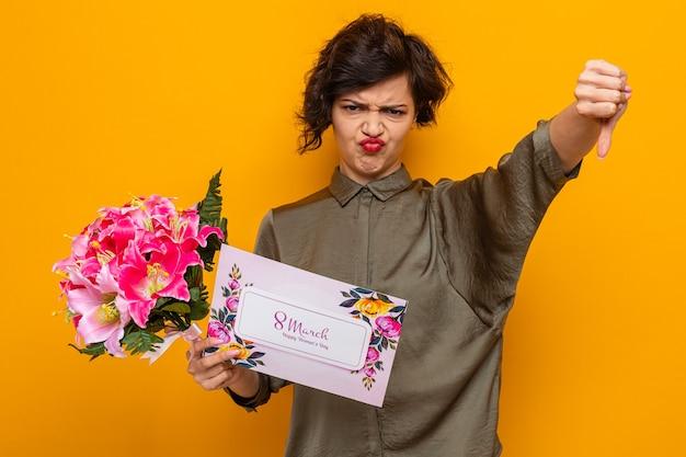 Женщина с короткими волосами, держащая поздравительную открытку и букет цветов, выглядит недовольной, показывает палец вниз, празднуя международный женский день 8 марта