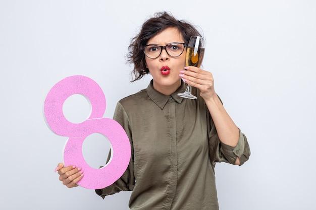 Donna con i capelli corti che tiene il numero otto realizzato in cartone e bicchiere di champagne guardando la telecamera sorpresa celebrando la giornata internazionale della donna l'8 marzo in piedi su sfondo bianco