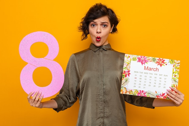 Woman with short hair holding paper calendar of month march and number eight looking confused and surprised celebrating international women's day march 8
