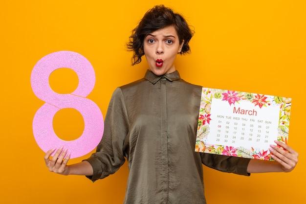 Женщина с короткими волосами, держащая бумажный календарь месяца март и номер восемь, выглядит смущенной и удивленной, празднуя международный женский день 8 марта