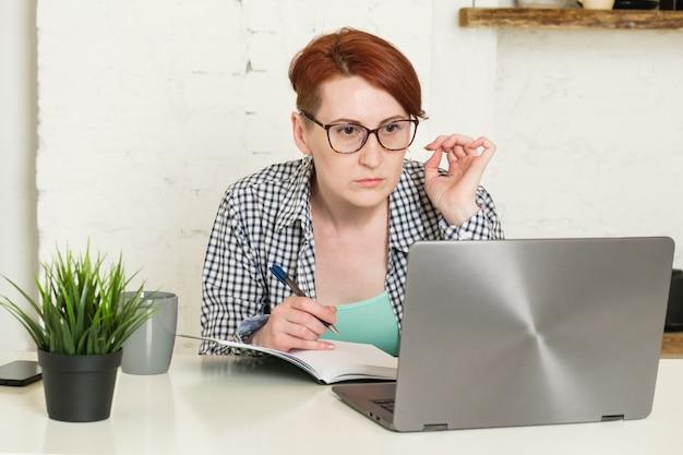 眼鏡をかけた短い髪の女性は、ノートパソコンの画面を注意深く見て、ノートにメモを取ります