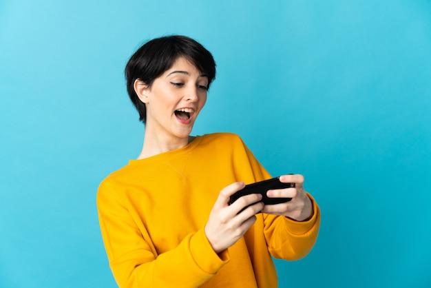 Женщина с короткими волосами изолирована, играя с мобильным телефоном